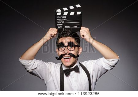 Young man with false moustache holding clapperboard isolated on