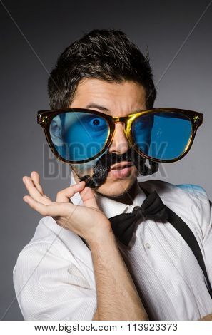 Young man with false moustache and large sunglasses isolated on gray