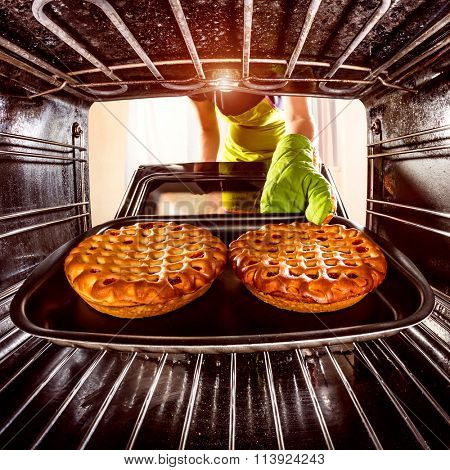 Housewife preparing cakes in the oven at home, view from the inside of the oven. Cooking in the oven.