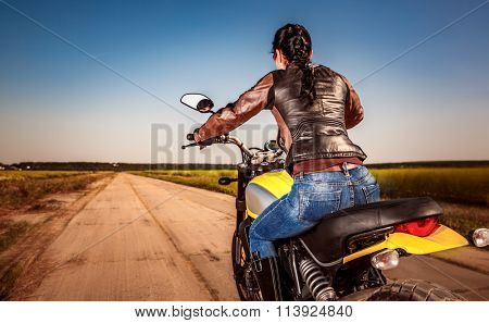 Biker girl in a leather jacket and helmet on a motorcycle