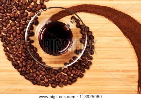 Coffee grains in the shape of a swirl with glass cup
