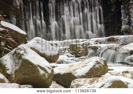Winter Waterfall In The Polish Mountains. River And Rocks Covered With Snow