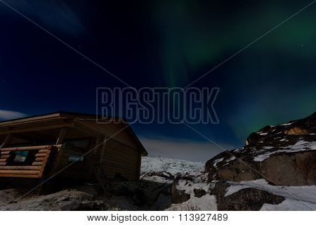 Wooden House On The Background Of The Aurora In Winter
