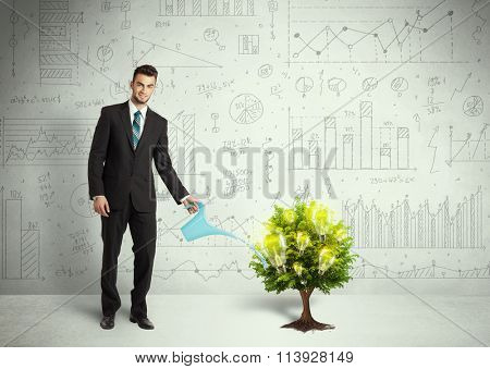 Business man pouring water on lightbulb growing tree concept