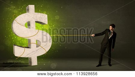 Business man pulling a big green dollar sign concept on background