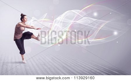 A beautiful young hip hop dancer dancing contemporary urban street dance in front of grey wall background with smokey lines and glitter concept.