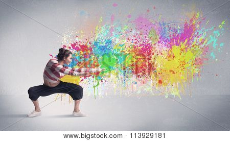 A Funky Contemporary Hip Hop Dancer Dancing In Front Of Grey Background With Colorful Bright Paint