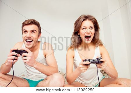 Young Couple In Love At Home Playing Games Joysticks And Laughing
