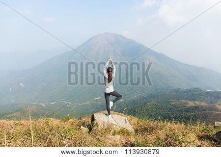 Asian Woman do yoga at the top of mountain