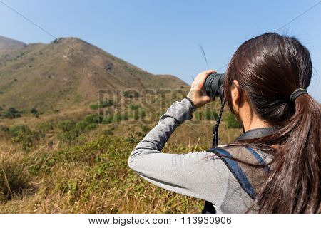 The back view of Young Woman use of the binocular