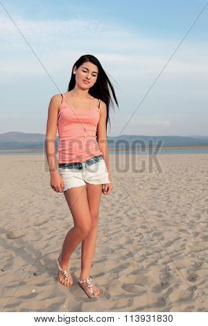 Young european teenage girl with long dark hair walking on a sandy beach in denim shorts and pink top.
