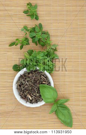 Fresh basil herb varieties with dried tulsi basil herbal medicine in a porcelain bowl over bamboo background.