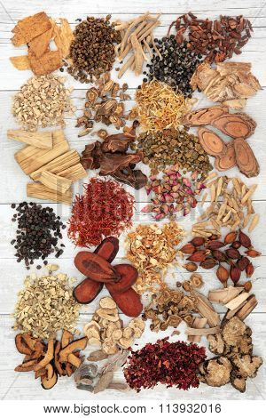 Chinese herbal medicine ingredients over distressed white wood background.