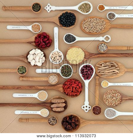 Dried superfood selection in spoons and bowls over natural paper background. Highly nutritious in antioxidants, minerals, vitamins and dietary fiber.
