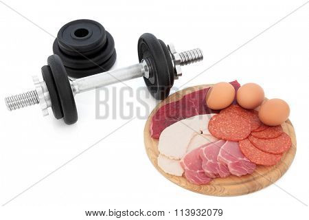 Body building high protein food of chicken, lean steak, bacon, salami and eggs with dumbbell weights over white background.