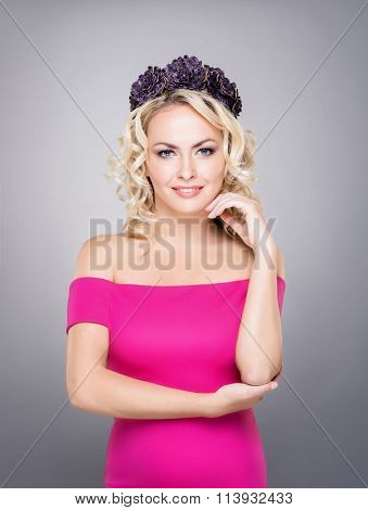 Portrait of gorgeous, young lady wearing pink dress and purple wreath over grey background.