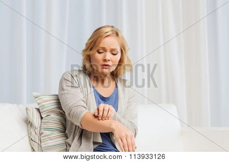 unhappy woman suffering from hand inch at home