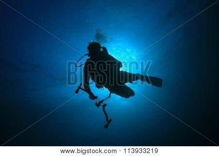 Scuba diver underwater photographer black on blue silhouette against sun