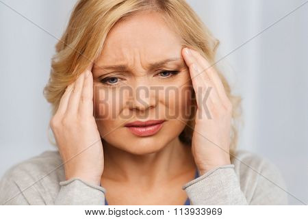 unhappy woman suffering from headache at home