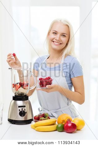 smiling woman with blender preparing shake at home