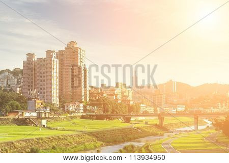 Beautiful suburb cityscape of Taipei with green grassland and river.