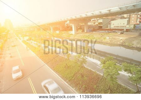 City traffic with cars motion blurred on road near bridge on river in daytime in Taipei, Taiwan, Asia.
