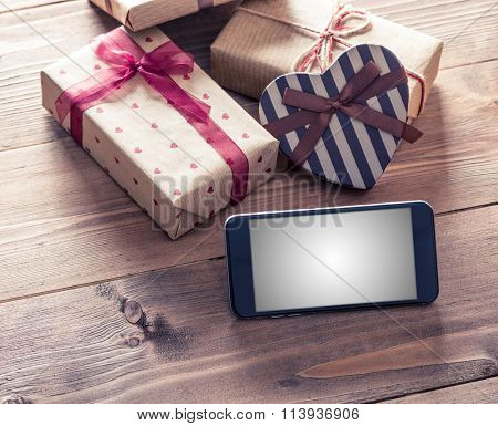 Black smart phone near gift boxes. Clipping path included.