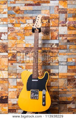 Music concept, electric guitar hanging on a brick wall