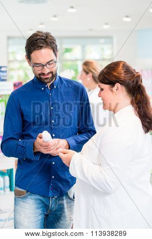 Pharmacist or drug store sales woman advising customer on care products for men