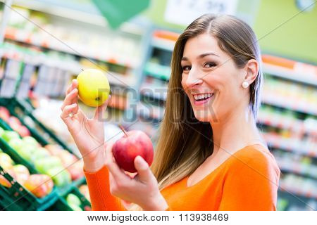 Woman selecting apples while grocery shopping in supermarket