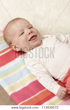 Closeup photo of smiling little baby lying on back.