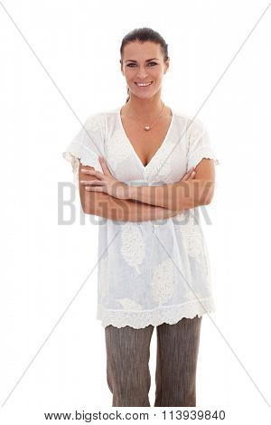 Portrait of brunette, casual businesswoman standing with arms crossed, looking at camera, white background.
