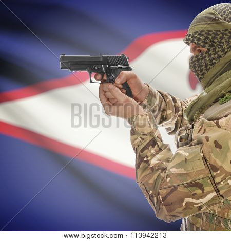 Male In With Gun In Hand And National Flag On Background - American Samoa
