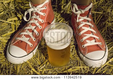 Female legs wearing red canvas sneakers and plastic cup of beer.