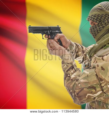 Male In With Gun In Hand And National Flag On Background - Guinea