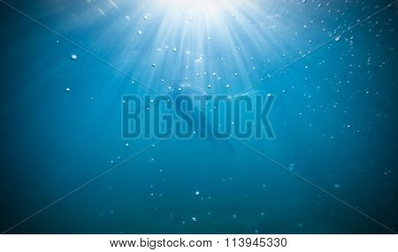 Silhouette of female freediver floating through sunbeams.