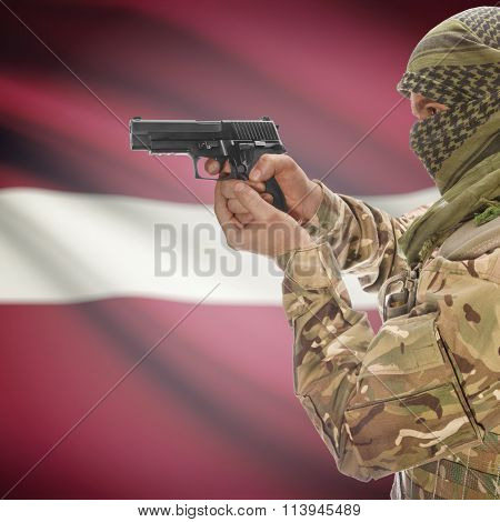 Male In With Gun In Hand And National Flag On Background - Latvia