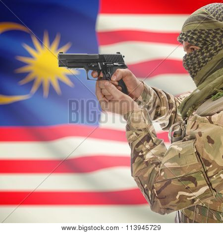 Male In With Gun In Hand And National Flag On Background - Malaysia