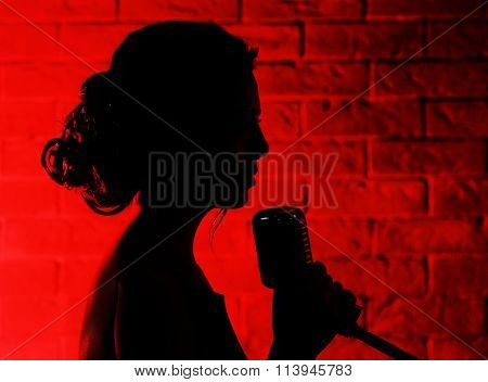 Silhouette of singing woman  on brick wall background
