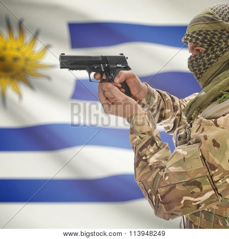 Male In With Gun In Hand And National Flag On Background - Uruguay