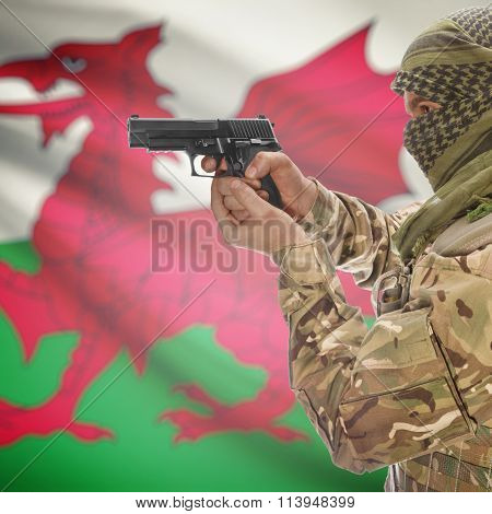 Male In With Gun In Hand And National Flag On Background - Wales