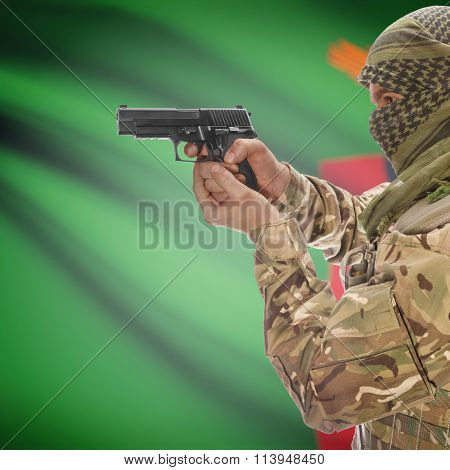 Male With Gun In Hand And National Flag On Background - Zambia