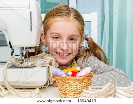 little seamstress sitting at the table with threads in basket and sewing machine