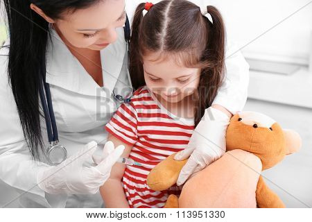 Doctor giving injection to the toy  bear
