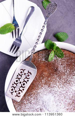 Chocolate pie with sugar powder and kitchenware, closeup