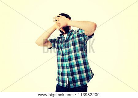 Young afraid man covering his face.