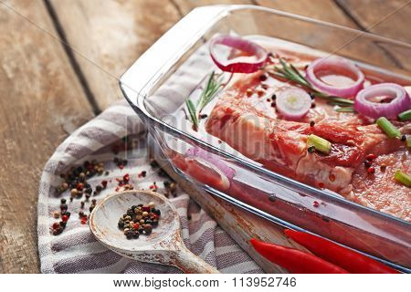 Marinating meat with spices on wooden table