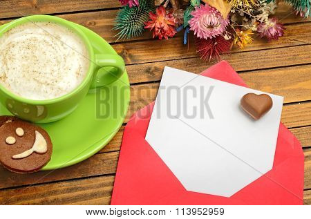 Red envelope with empty paper and cappuccino cup on table