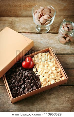 White chocolate morsels in box on wooden background