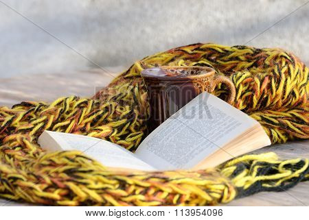 Still life from a cup of tea, muffler and book